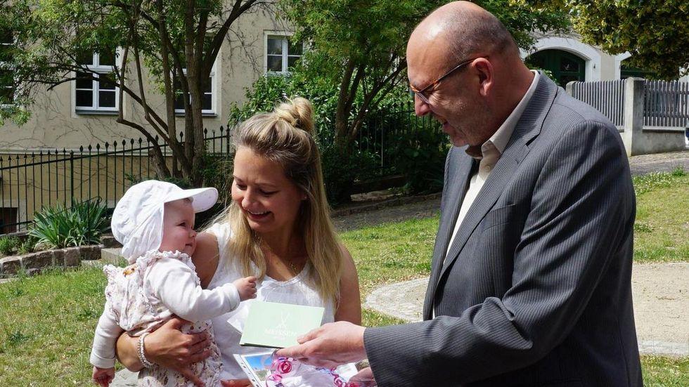 Ella Carlotta Roßkamp auf dem Arm von Mama Nicole nimmt die erste Begrüßungsmedaille von Oberbürgermeister Olaf Raschke entgegen. Quelle: Presse Stadt Meißen