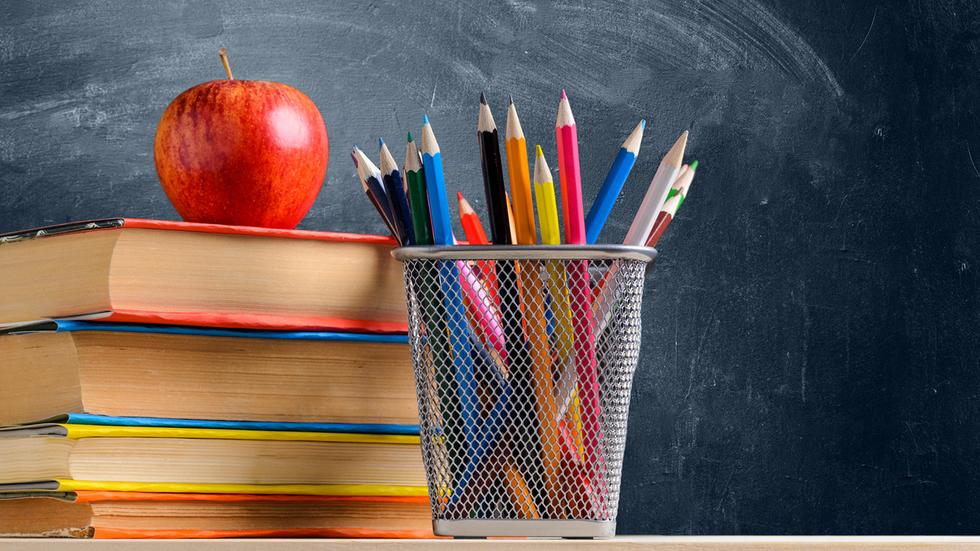 gestapelte Schulbücher, Stifte im Köcher, Apfel