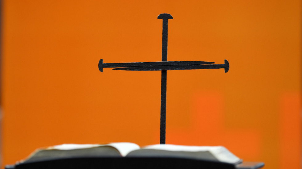 Ein Nagelkreuz steht hinter einer Bibel auf einer Bühne vor der Gedächtniskirche.