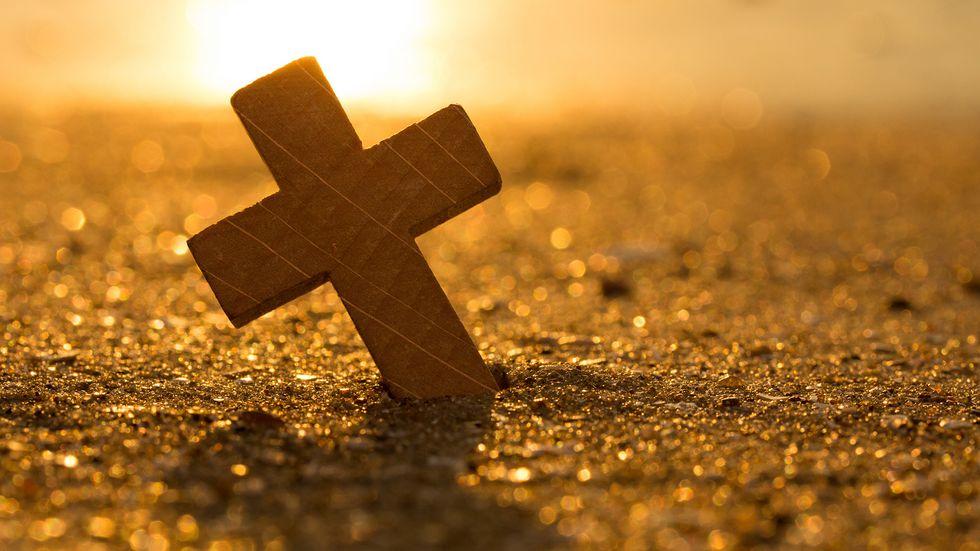 Kreuz steckt im Sand